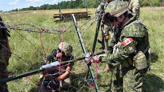 Canadian and Ukrainian Combat Engineers prepare explosive charges during obstacle demolition training at the International Peacekeeping and Security Centre in Starychi, Ukraine, on August 20, 2016