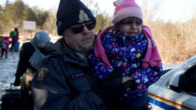 Un agent de la GRC emmène dans ses bras un enfant d'une famille qui dit être originaire du Yémen lors de leur arrivée à la frontière entre les États-Unis et le Canada à Hemmingford, au Québec, ce dimanche. (Christinne Muschi / Reuters)