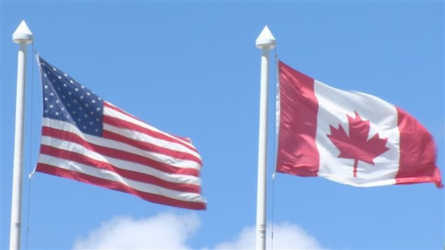 Des drapeaux américain et canadien flottent sur le terrain du centre commercial Bellis Fair à Bellingham dans l'État de Washington.
