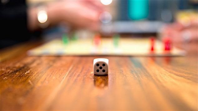 Un dé à jouer posé sur une table avec en arrière plan un plateau de jeu.