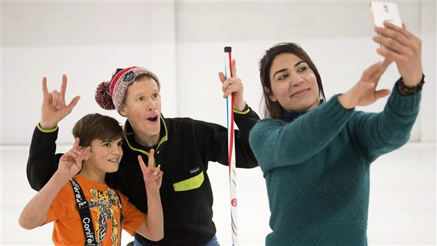 A Yazidi Kurdish woman and her son pose for a photo with curling club member Jim Creeggan (centre).