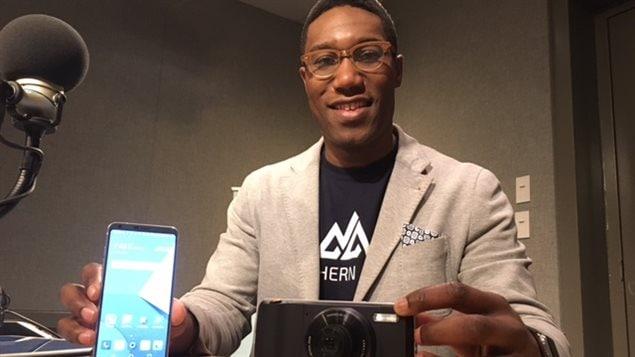 Carl-Edwin Michel présente deux téléphones intelligents.
