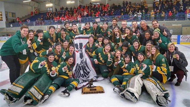 Une équipe de hockey féminine célèbre sa victoire sur la patinoire.