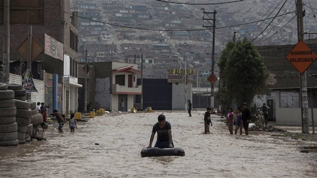 Flood waters run in the streets of Lima, Peru on March 16, 2017. Unusually heavy rains killed at least a dozen people. Authorities blamed the warming of the Pacific Ocean.