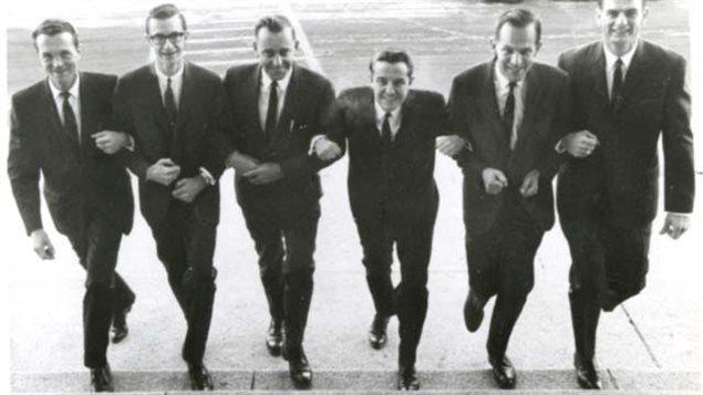 Six hommes marchant bras dessus, bras dessous.