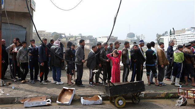 Civiles hacen fila en Mosul para recibir ayuda humanitaria en el distrito Al Ghizlane, mientras avanzan las fuerzas iraquíes en el oeste de Mosul, el 20 de marzo de 2017.