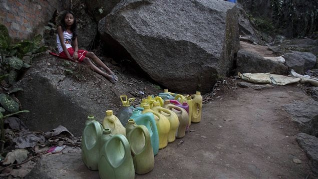 An Indian girl waits for the arrival of water at a public tap in Gauhati, India. There is no direct supply of drinking water at homes in most of the country's poor neighbourhoods.