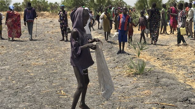 Lulu Yurdio gets food aid for himself and family members who are hiding in the bush in Padeah, South Sudan. They have fled famine and fighting in Leer county.
