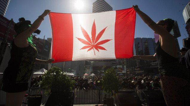 Deux femmes tiennent un drapeau du Canada où la feuille d'érable a été remplacée