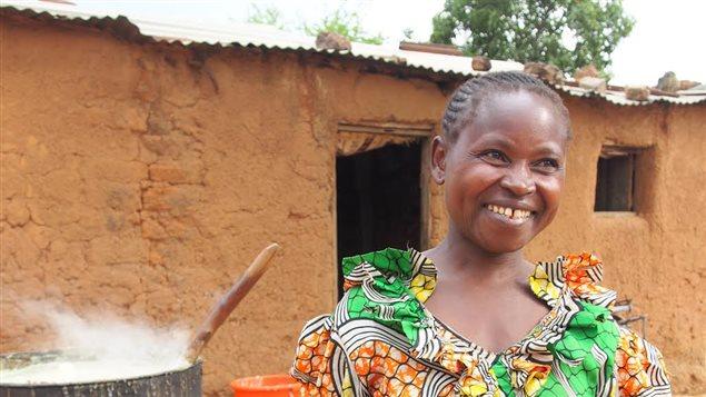 Photo d'une femme africaine devant une maison