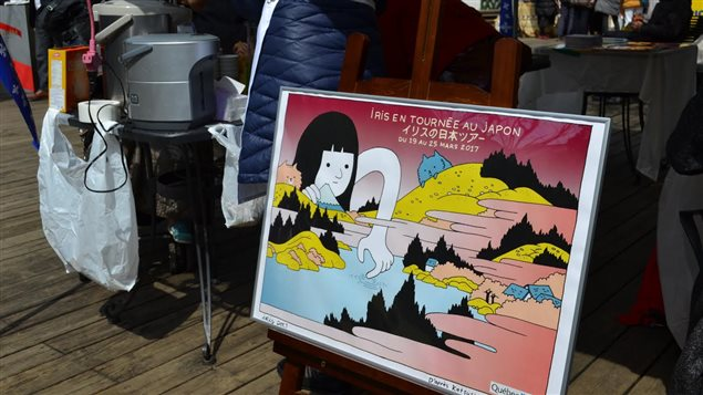 En premier plan, une affiche de promotion dans le cadre de la tournée de la bédéiste Iris au Japon, et en arrière plan, des kiosques dans un marché à Tokyo