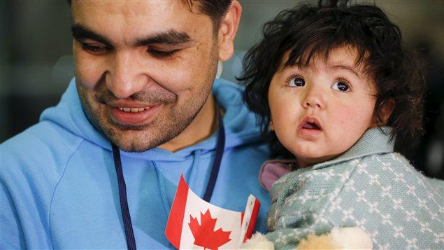 Un padre y un niño inmigrante con una bandera canadiense.