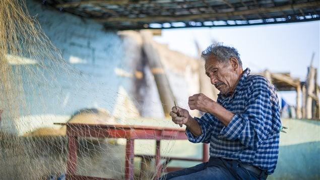 Pescador peruano preparando y reparando su atarraya.