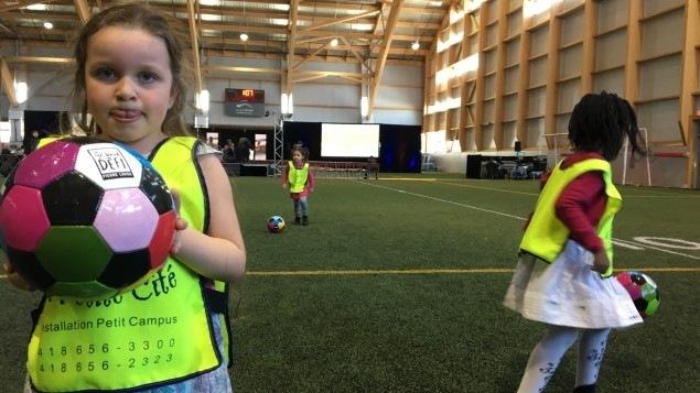 Une fillette tient un ballon de soccer dans ses mains au PEPS
