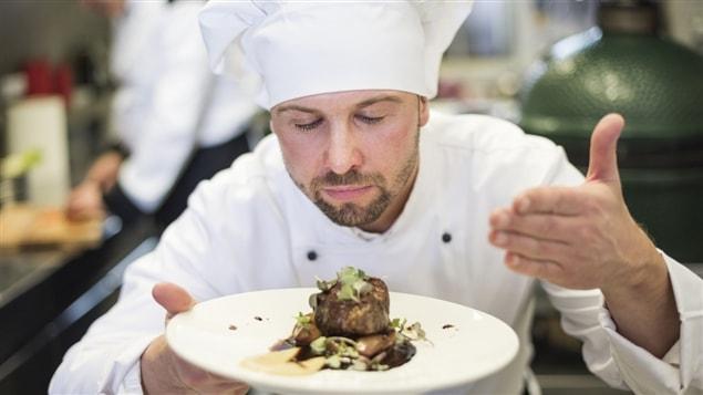Un chef hume le plat qu'il s'apprête à servir.