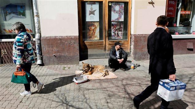 Un hombre sentado a lado de su perro, pidiendo ayuda en Krasnoyarsk, Siberia, Rusia.