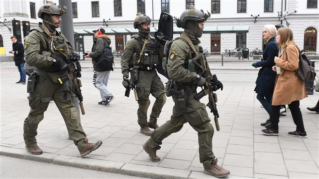 Armed police patrol outside the central station in Stockholm after a truck crashed into a department store injuring several people in a different part of Stockholm, Sweden, Friday April 7, 2017.