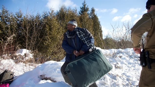 In February, this man who said he was originally from Sudan, crossed with his family into Quebec under the eyes of a US border guard. He only has to cross a shallow ditch to enter Canada at this unguarded road. Aid agencies say most asylum seekers end up in Toronto.