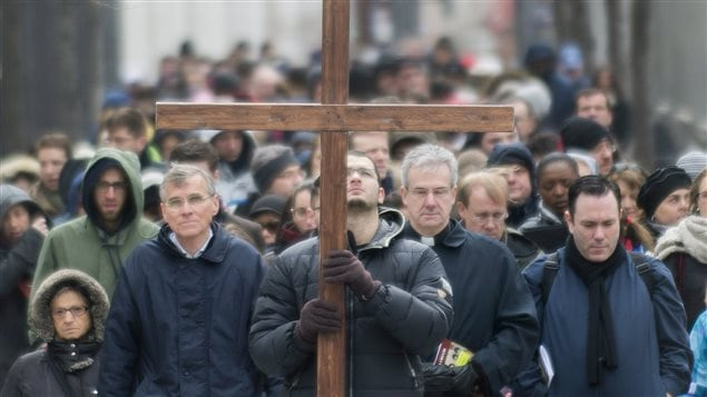 A man walks with a crucifix along with the faithful as they participate in the Way of the Cross on Good Friday in Montreal, April 18, 2014.