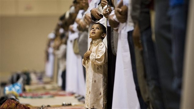 Zubar Karamat, 3, looks up during prayer at the Muslim Association of Canada's Eid celebration at the Metro Convention Centre in Toronto on Tuesday, August 30, 2011.