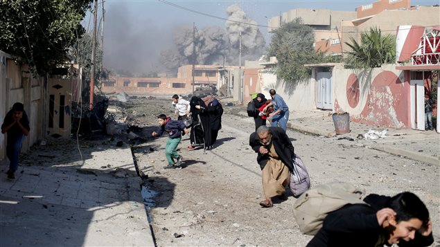 People run in panic after a coalition airstrike hit Islamic State fighters positions in Mosul, Iraq, November 17, 2016.