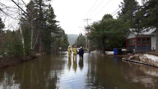 Les pompiers et les résidents évaluent les inondations sur le Chemin de la Rivière à Val-Morin, situé dans les Laurentides. (Sudha Krishnan / CBC)