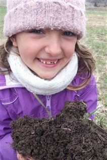 Alan Kruszel's daughter Stephanie holds some very healthy soil.