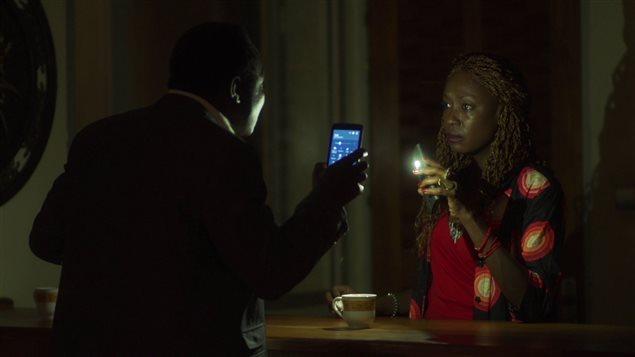 Une femme et un homme se regardent en tenant chacun un téléphone cellulaire dans le noir