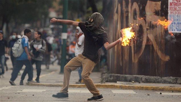 Manifestante lanza un coctel Molotov durante los enfrentamientos con las fuerzas del orden el 20 de abril 2017.