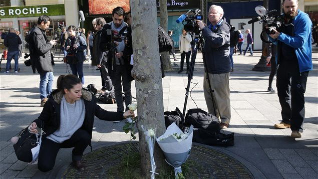 A woman lays a flower at the place of Thursday's attack on the Champs Elysees boulevard in Paris, Friday, April 21, 2017.