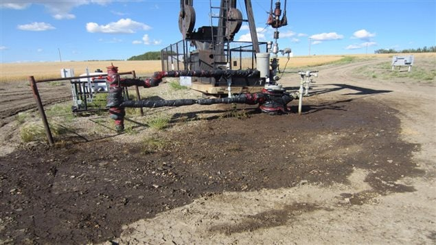 Active oil well that appears to have suffered a blow out. The ground around the wellhead is soaked with oil and wellhead and attached pipes are wrapped in plastic sheathing