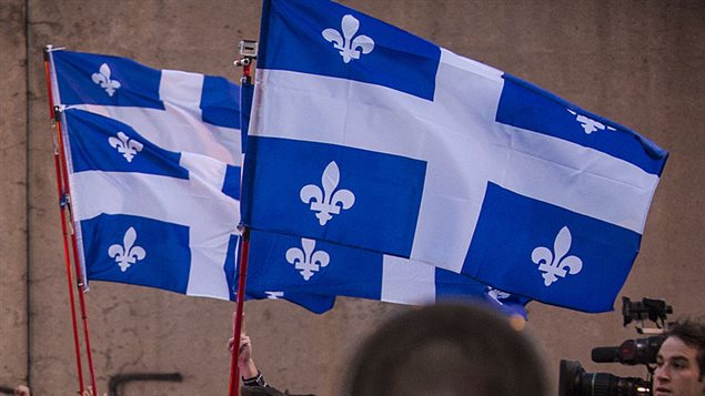 Des gens portent un drapeau du Québec lors d'une manifestation à Montréal