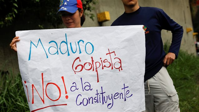 Opposition supporters hold a placard that reads, *Maduro, coup-monger. No to the constituent assembly*, during a protest against Venezuela's President Nicolas Maduro's government in Caracas, Venezuela May 2, 2017.