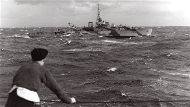 A merchant seaman watches Canadian river-class destroyer HMCS Swansea on convoy escort duty in the north Atlantic. On April 14,1944 Swansea and HMS Pelican sank U-448