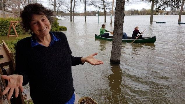 Nicole David Strauss devant sa maison. Ce qui devrait être une rue, est actuellement totalement englouti par la crue de la rivière des Prairies.