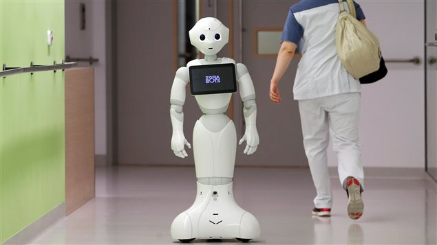 A nurse walks by new recruit *Pepper* the robot, a humanoid robot designed to welcome and take care of visitors and patients, at AZ Damiaan hospital in Ostend, Belgium June 16, 2016.