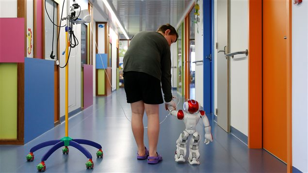 Belgian Ian Frejean, 11, walks with *Zora* the robot, a humanoid robot designed to entertain patients and to support care providers, at AZ Damiaan hospital in Ostend, Belgium June 16, 2016.