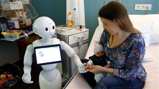 New recruit *Pepper* the robot, a humanoid robot designed to welcome and take care of visitors and patients, holds the hand of a new born baby next to his mother at AZ Damiaan hospital in Ostend, Belgium June 16, 2016.