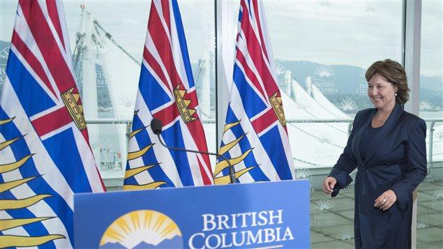 La première ministre Christy Clark marche vers un podium avec des drapeaux de la province en arrière-plan.