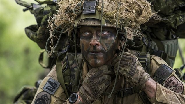 Master Corporal Audie Ste. Croix from 1st Battalion, The Royal Canadian Regiment, dressed as enemy force for the exercise, adjusts his helmet during Exercise MAPLE RESOLVE in Wainwright, Alberta on 1 June, 2016.