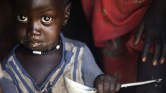 A boy eats out of a ladle at his home in Ngop in South Sudan's Unity State on March 10, 2017.