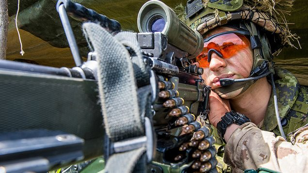 Private Nichola Goulet, a member of 1st Battalion, The Royal Canadian Regiment, looks through a C9 machine gun during Exercise MAPLE RESOLVE at Wainwright, Alberta on June 2, 2016.
