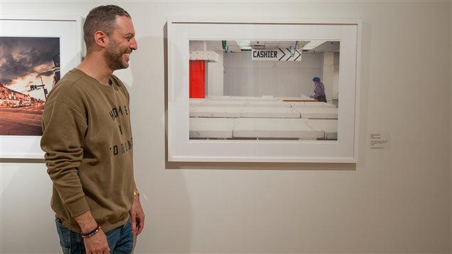 Le photographe Vladimir Antaki pose devant sa photo prise à Honest Ed's.