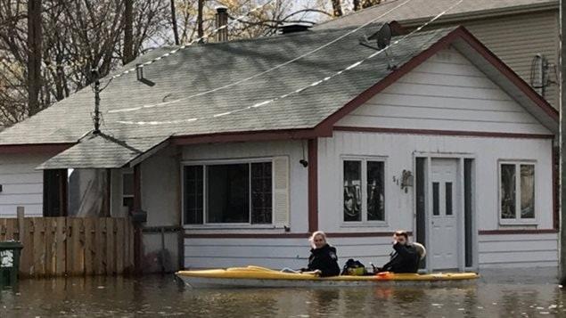La familia regresa en kayak para recuperar algunas cosas en su casa inundada.