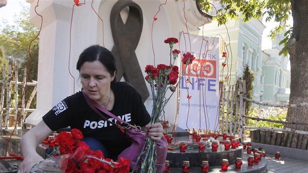 Mujer deposita flores en el monumento dedicado a las víctimas del Sida en Kiev, Ucrania, el 19 de mayo 2017.