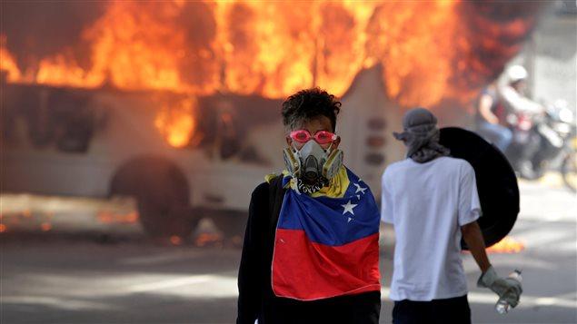 Manifestantes de la oposición junto a un autobús de transporte público incendiado durante una protesta contra el gobierno del presidente venezolano Nicolás Maduro en Caracas, Venezuela, el 13 de mayo de 2017.