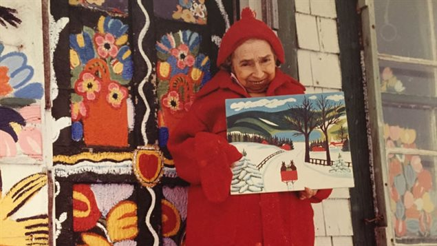 Maud Lewis standing in front of her home with one of her paintings