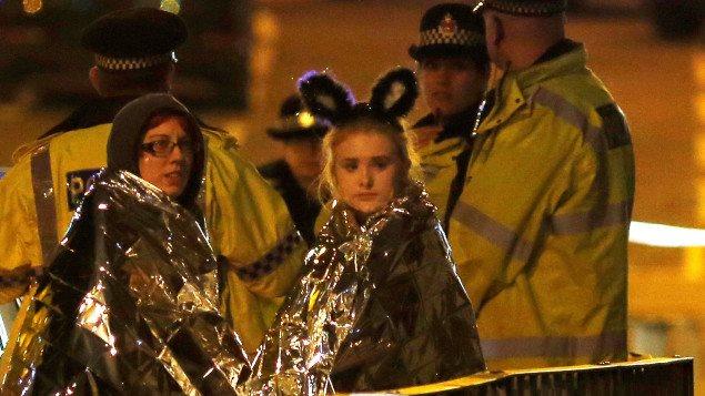Deux jeunes femmes enveloppées dans des couvertures thermales à la sortie du Manchester Arena.