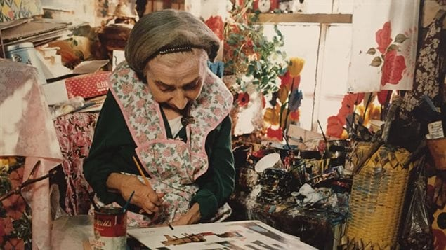 Maud Lewis painting in her home in spite of arthritis