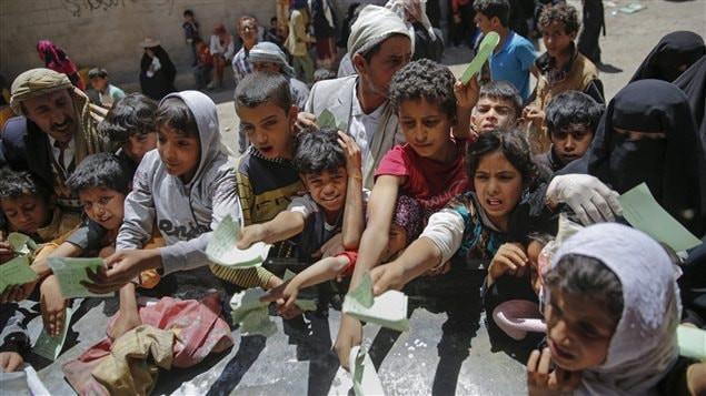Yemenis wait for food rations as the two-year conflict has pushed the county to the brink of famine.